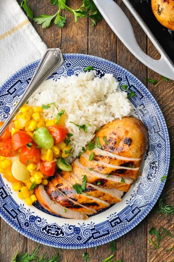 Close overhead shot of marinated lemonade chicken recipe served with rice on a blue and white plate
