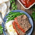 Meatloaf recipe with oatmeal on a blue and white dinner plate with mashed potatoes and green beans