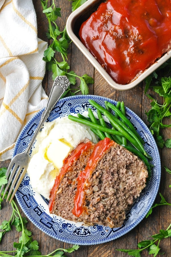 Two slices of meatloaf recipe with oatmeal on a blue and white dinner plate