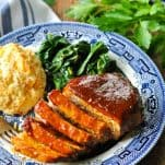 Front shot of oven bbq pork chop on a plate with biscuit and greens