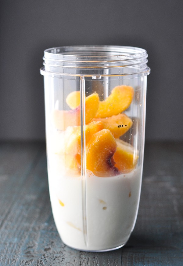 Front shot of ingredients for peach smoothie in a blender