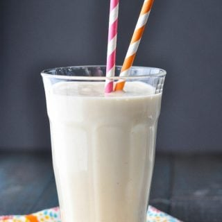 Close up front shot of a peach smoothie in a glass with pink and orange straws