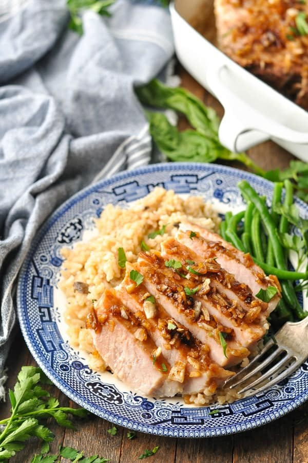 Baked pork chop on a plate with rice and green beans
