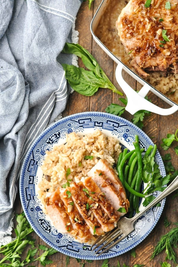 Overhead shot of sliced pork chop and rice bake on a blue and white plate