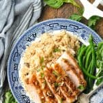 Close overhead shot of pork chops and rice on a plate on a wooden table