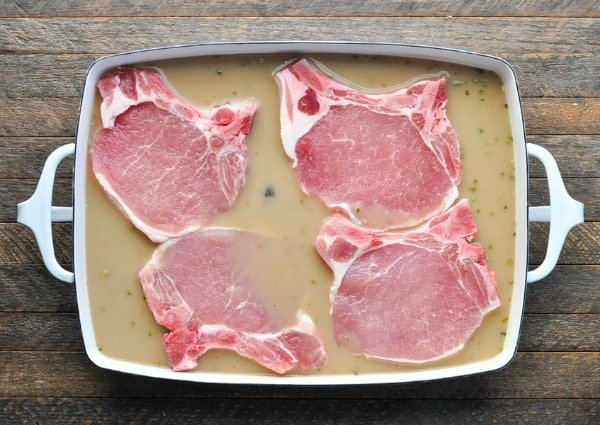 Raw pork chops in a casserole dish before baking