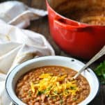 Ranch style beans in a white bowl with a red Dutch oven in the background