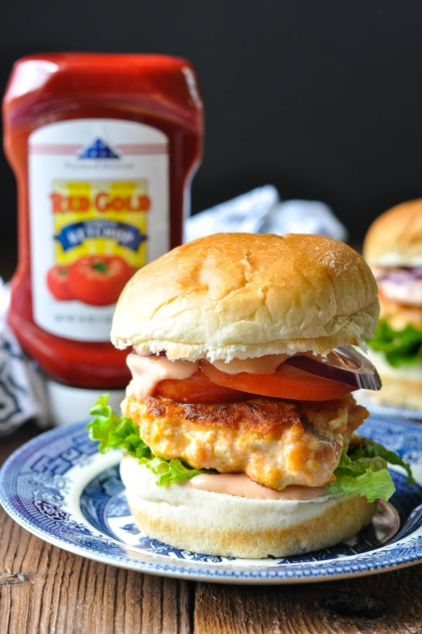 Close up front shot of a salmon burger on a bun with toppings and sauce