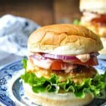Salmon burger on a bun piled high with toppings and salmon burger sauce