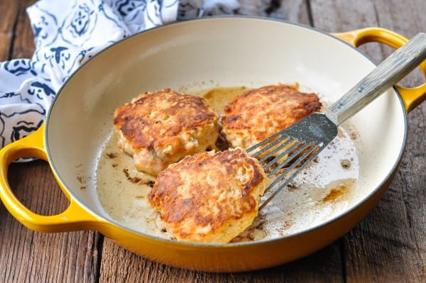 Salmon burgers cooked in a cast iron skillet