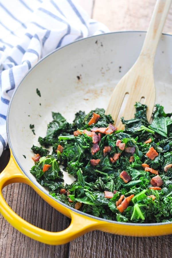 Side shot of sauteed kale with bacon in a skillet with a wooden spoon