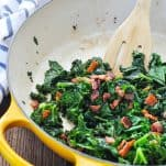 Sauteed kale in a yellow skillet with wooden spoon