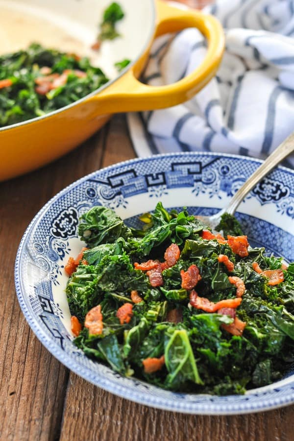 Close side shot of a bowl of southern kale greens with bacon