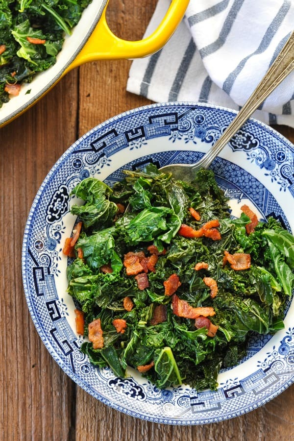 Close overhead shot of sauteed kale with bacon in a blue and white bowl