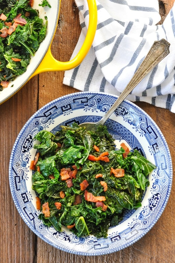 Overhead shot of sauteed kale in a blue and white bowl topped with crispy bacon