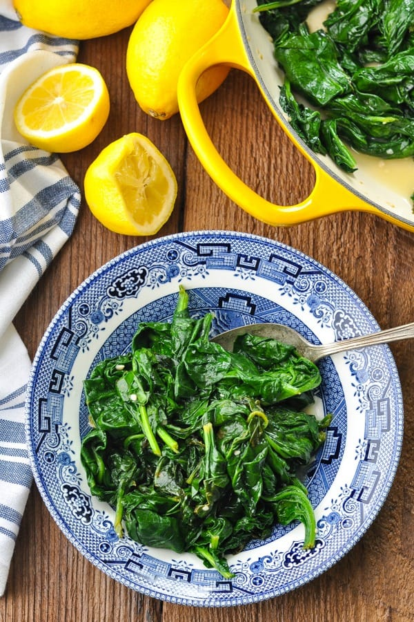 Close overhead shot of a bowl of sauteed spinach with garlic and fresh lemon
