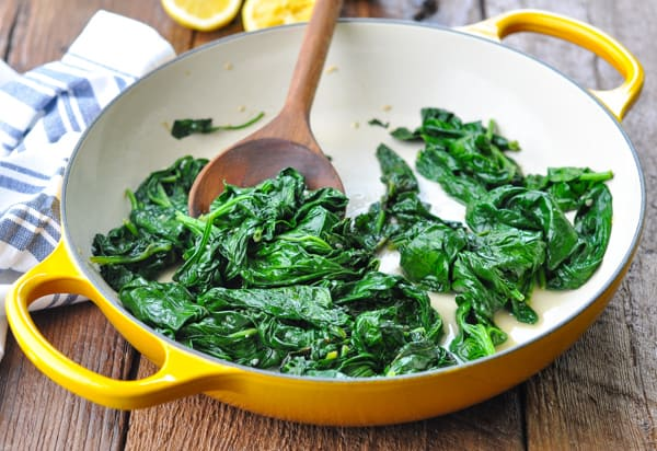 Horizontal shot of sauteed spinach with garlic in a skillet with a wooden spoon