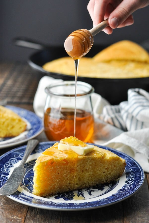 Drizzling honey over a slice of skillet cornbread