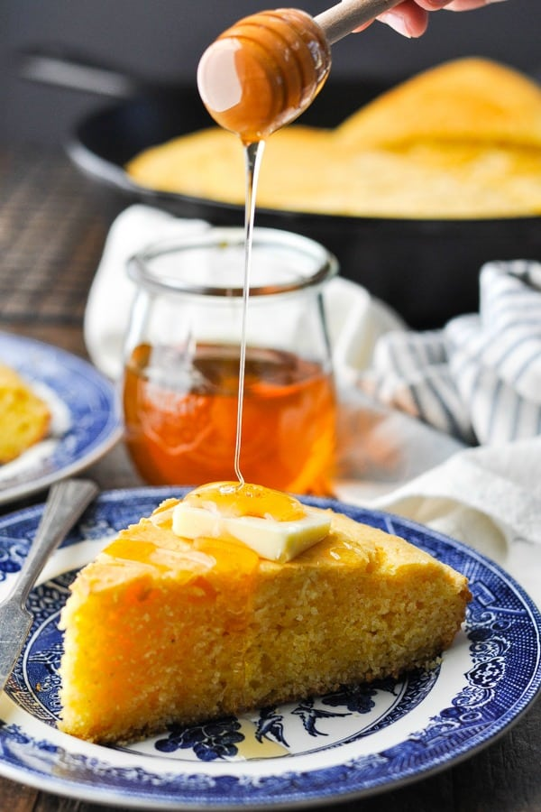 Pouring honey over a slice of cornbread