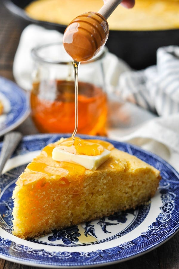 Close up front shot of drizzling honey over skillet cornbread on a blue and white plate