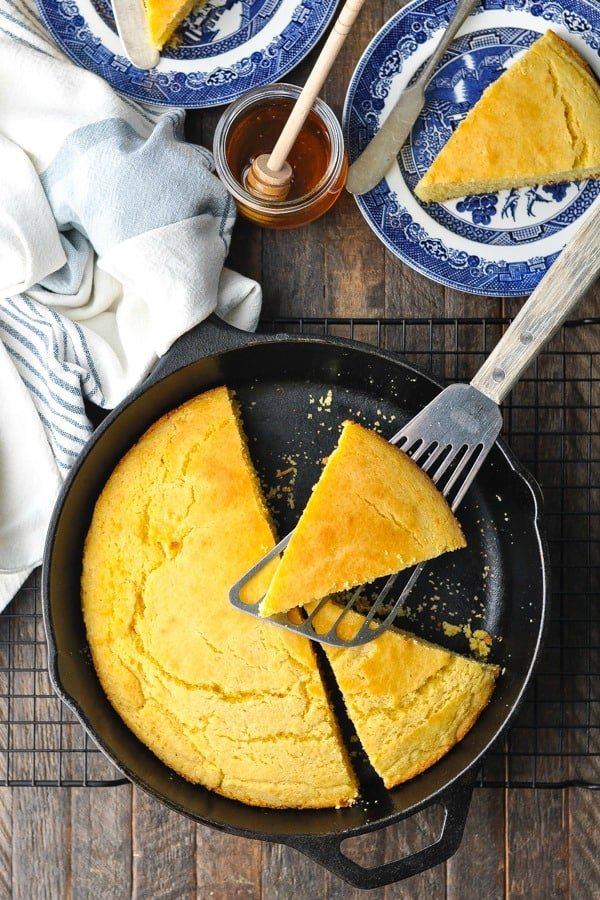 Overhead shot of a slice of cast iron skillet cornbread on a spatula