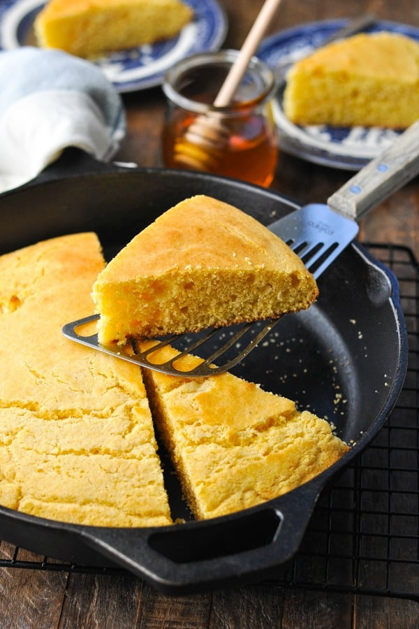 Front shot of skillet cornbread wedge on a spatula