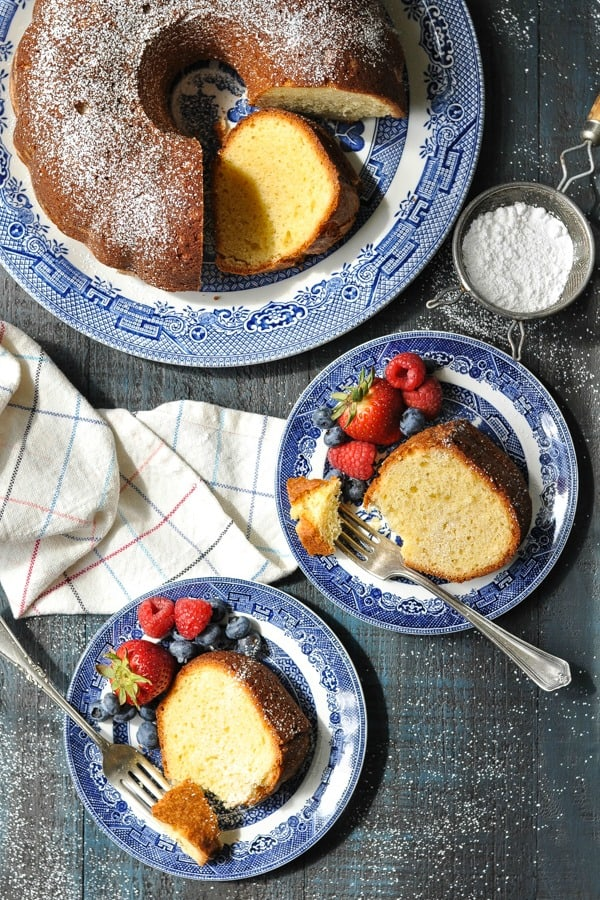 Overhead image of two slices of pound cake on blue and white plates with berries