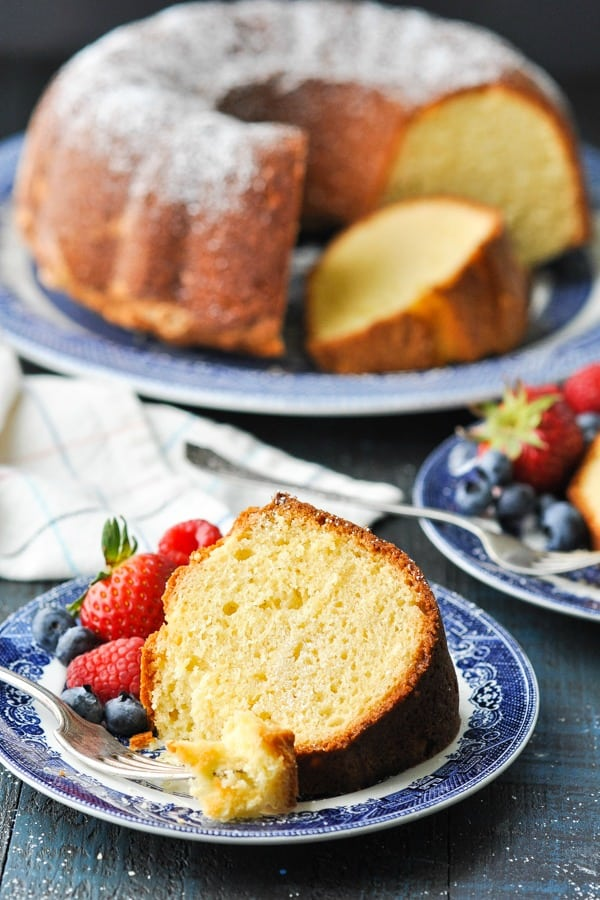 Slice of sour cream pound cake on a blue and white plate with fresh berries