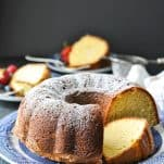 Front shot of a sliced sour cream pound cake on a blue and white plate
