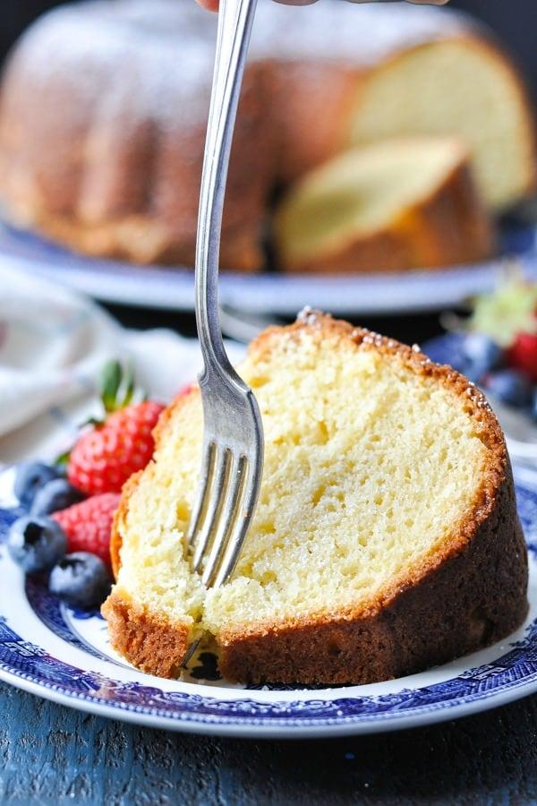 Fork digging into a slice of sour cream pound cake