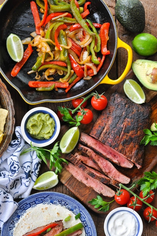 Overhead shot of steak fajitas and toppings on a wooden table