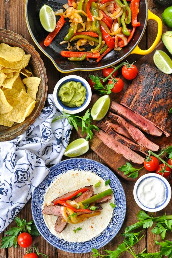 Grilled steak fajitas recipe on a wooden table with sides