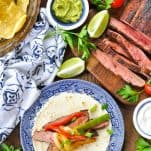Overhead shot of a steak fajitas recipe on a table surrounded by limes chips and guacamole