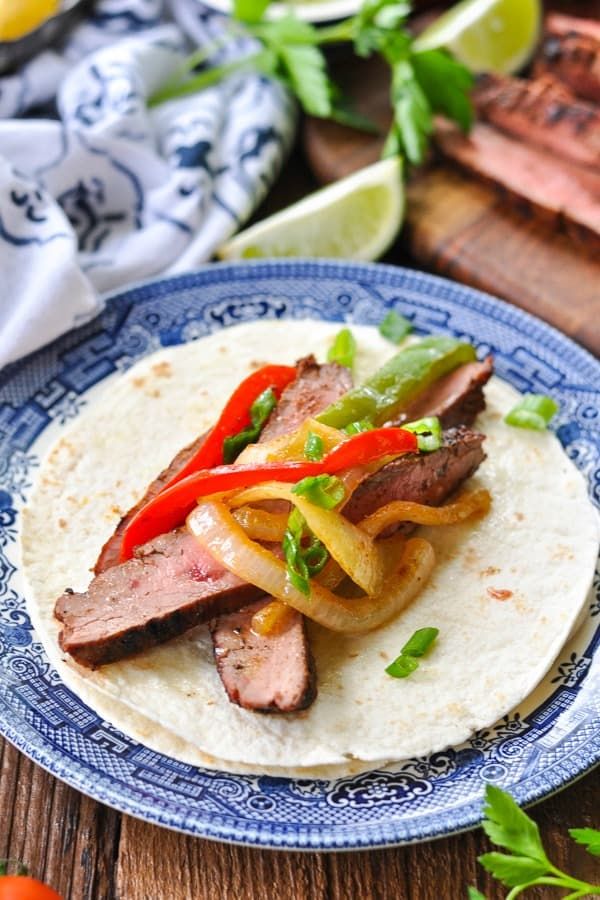 Front shot of a flour tortilla with steak and vegetables for a fajita on a plate