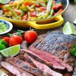 Front shot of sliced grilled flank steak on a cutting board for steak fajitas
