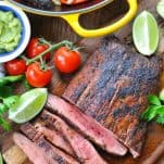 Overhead shot of steak fajitas recipe on a wooden table surrounded by fresh vegetables and limes