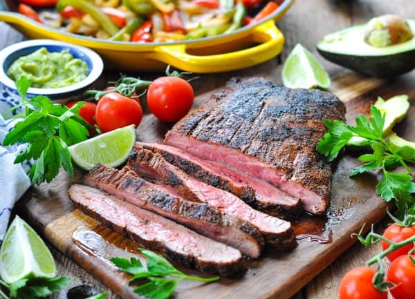 Horizontal shot of sliced flank steak on a cutting board for fajitas