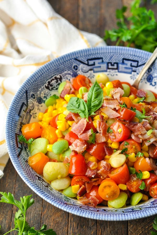 Close up front shot of succotash recipe garnished with bacon