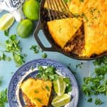 Overhead image of tamale pie with a cornbread crust surrounded by limes and parsley