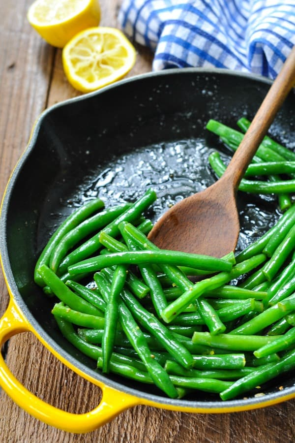 Cooking fresh green beans in a cast iron skillet with butter