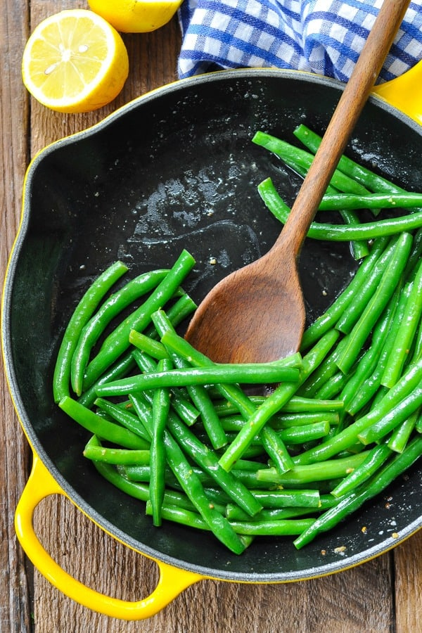 Overhead shot of Amish Green Beans with Brown Butter in a cast iron skillet with a wooden spoon