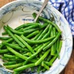 Overhead shot of green bean recipe served in a bowl on a wooden table