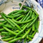 Bowl of green beans with lemon in a bowl with a silver serving spoon