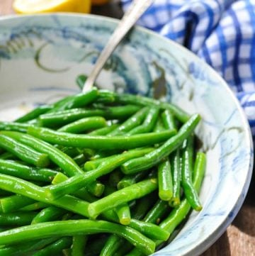 Side shot of a bowl of fresh green beans cooked with brown butter and lemon