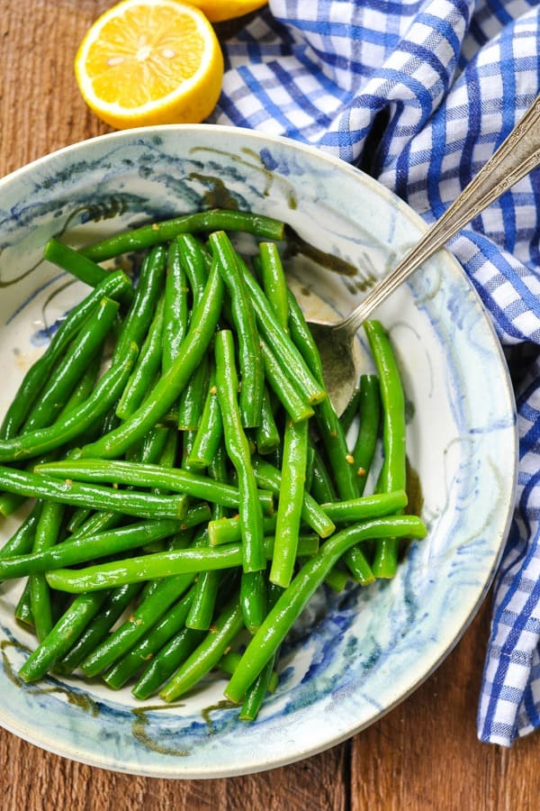 Overhead shot of a green bean recipe in a bowl with a blue and white checked napkin nearby