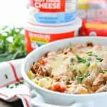 Quick and easy amish hamburger casserole in a white dish with cottage cheese containers in the background
