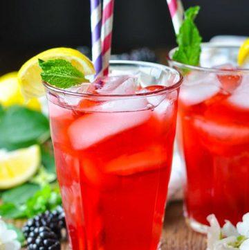 Two glasses full of blackberry lemonade with mint garnish