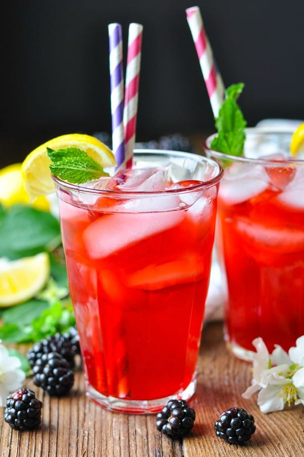 Two glasses full of blackberry lemonade with mint garnish