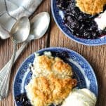Overhead shot of warm blueberry cobbler recipe served on two blue and white plate with vanilla ice cream