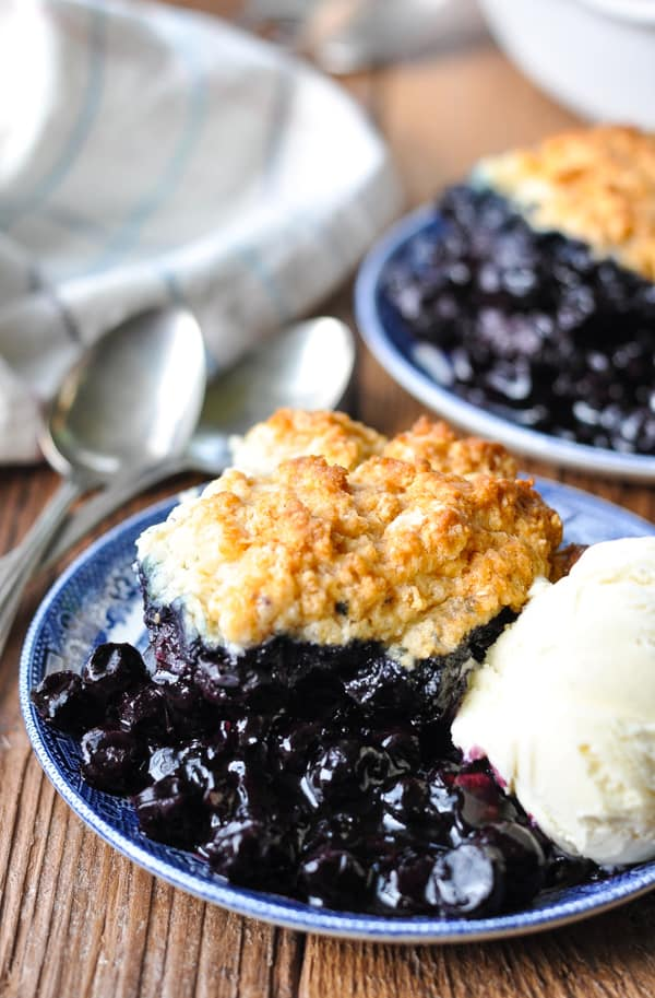 Front shot of a plate of old fashioned blueberry cobbler with a scoop of ice cream
